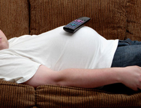 huevon man sleeps on couch with remote on his belly